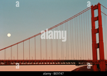 Moon set behind Golden Gate Bridge in San Francisco Bay, California, USA - Stock Image