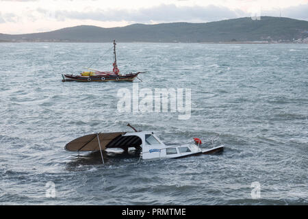 Moored boat partially sunk from storm force winds on the Aegean coast in Ayvalik, Turkey - Stock Image