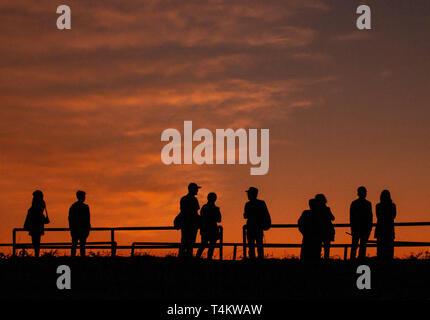 Silhouettes of people against an orange sunset sky, Bagan, Myanmar. - Stock Image