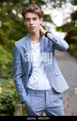 Young man in casual suit standing in park, looking away - Stock Image