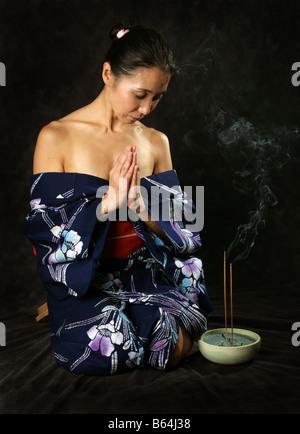 Japanese Woman in a Blue Kimono, Kneeling and Praying - Stock Image