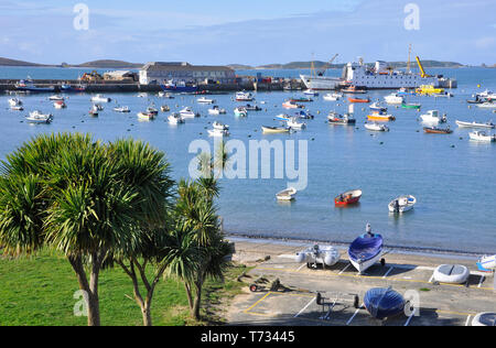 View across the harbour at Hugh Town, St Mary's,Isles of Scilly. Scillonian III being loaded prior to leaving for Penzance. - Stock Image
