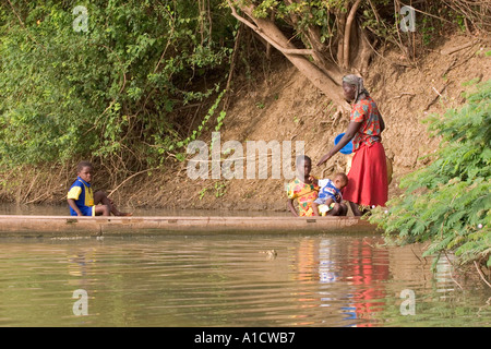 Mother and children about to travel by canoe on the Black Volta river in north western Ghana - Stock Image