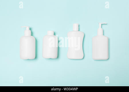 Set of White Cosmetic containers isolated on blue background, top view with copy space. Group of plastic bodycare bottle containers with empty space f - Stock Image