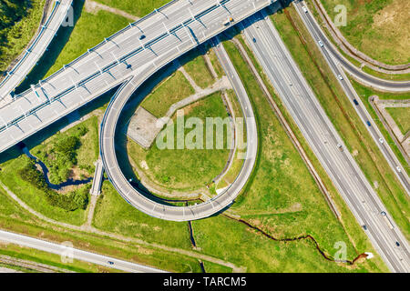 Big road junction fragment on green land aerial view, Highway intersection with traffic at sunny day - Stock Image