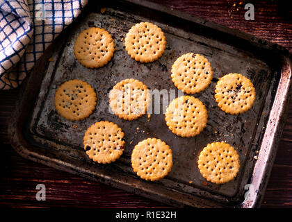 Fresh from the oven  Biscuits on a baking tray - Stock Image