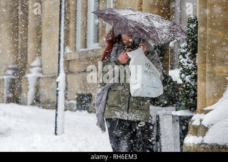 Chippenham, Wiltshire, UK. 1st February, 2019. A woman is pictured as she braves heavy snow showers in Chippenham town centre. Credit: Lynchpics/Alamy Live News - Stock Image