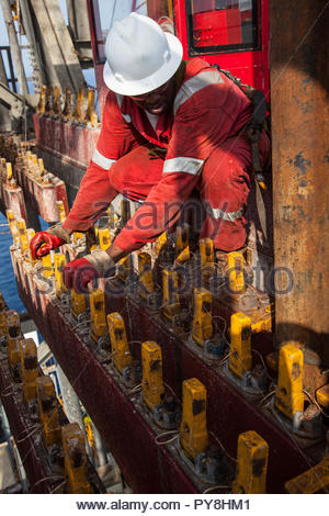Worker crouched on offshore oil platform - Stock Image