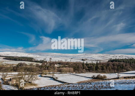 North Pennines AONB Landscape. Snow covered meadows, cirrus clouds bright winter sunshine and a deep blue sky at Bowlees, Teesdale - Stock Image
