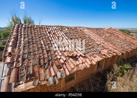 roof of building depressed with old clay tiles broken and blue sky - Stock Image