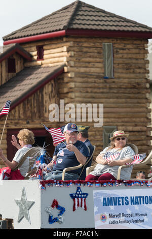 Anchorage, Alaska. 4th July, 2018. Military veterans pass a log building as they ride in a float during the annual Independence Day parade July 4, 2018 in Anchorage, Alaska. Credit: Planetpix/Alamy Live News - Stock Image
