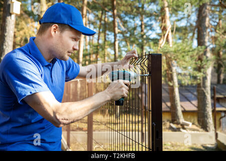 fencing services - worker installing welded metal mesh fence - Stock Image
