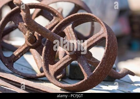 Reclaimed, aged iron wheels - Stock Image