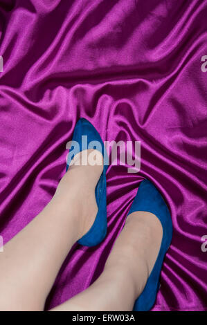 POV Women's lower legs wearing blue shoes with rich purple satin base - Stock Image