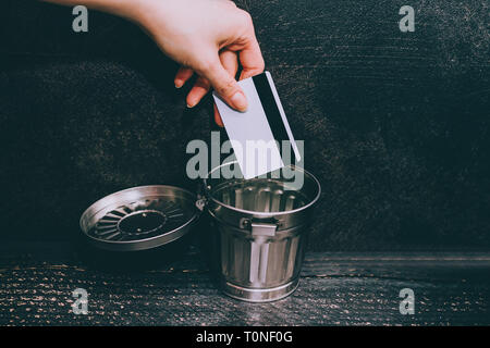 credit card going into a garbage bin, concept of financial instability or excessive shopping - Stock Image