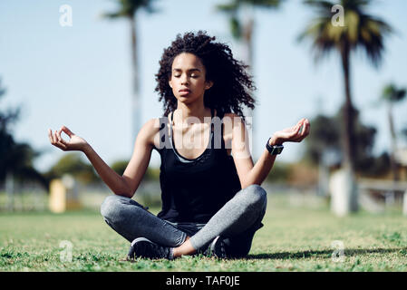 Sporty young woman doing yoga on lawn - Stock Image