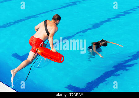 Lifeguard in action, entering water. - Stock Image