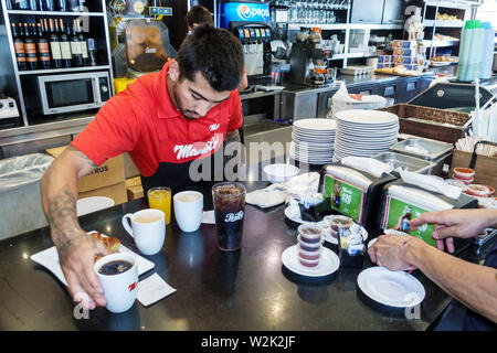 Miami Beach Florida North Beach Collins Avenue Manolo Argentinian restaurant interior inside counter Hispanic man employee preparing order - Stock Image