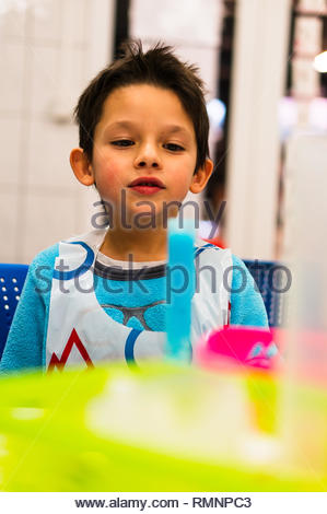Poznan, Poland - February 2, 2019: Young boy looking at a tube with blue liquid during experiment lessons. - Stock Image