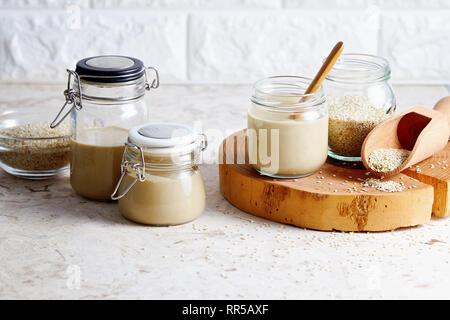 Homemade tahini in glass jars (sesame seed paste). - Stock Image