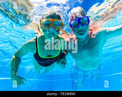Adult people senior couple have fun swimmin in the pool underwater with coloured funny diving masks - dive concept and active retired man and woman en - Stock Image
