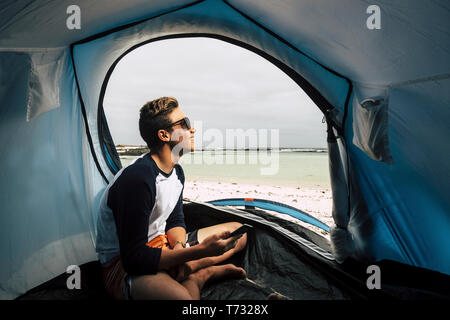 Young handsome boy enjoying the freedom in a tent camping at the beach in tropic paradise - phone mobile device on hand to stay in contact with intern - Stock Image