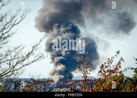 House on fire in a city with black smoke covering the sky in the daytime - Stock Image