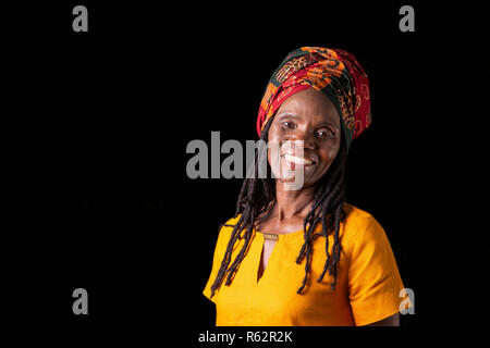 An elderly African woman in a headscarf against a black background - Stock Image