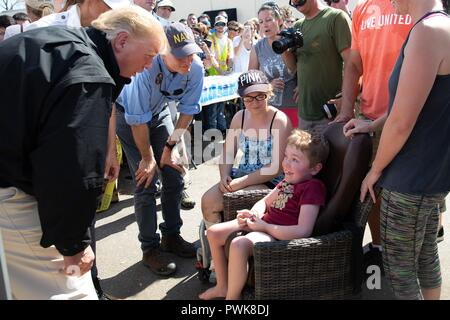 Panama City, Florida, USA. 15th Oct 2018. U.S President Donald Trump and Florida Gov. Rick Scott chat with a young boy during a visit with victims of Hurricane Michael October 15, 2018 in Lynn Haven, Florida. Credit: Planetpix/Alamy Live News - Stock Image