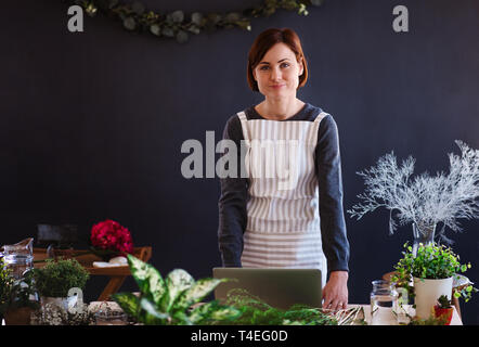 A young creative woman arranging flowers in a flower shop. A startup of florist business. - Stock Image