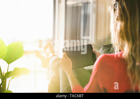 Woman relaxing in armchair at home holding tablet - Stock Image