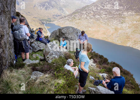 Hikers resting on Mt Tryfan north ridge overlooking Llyn Ogwen Lake in mountains of Snowdonia National Park. Ogwen, Conwy, Wales, UK, Britain - Stock Image