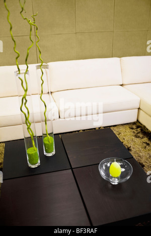 Showpieces on a table with a couch - Stock Image