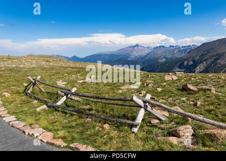 Bright, sunny Colorado Rocky Mountains, with rail fence and rock field in front, dramatic, blue-grey mountains beyond, with bright blue sky and clouds - Stock Image