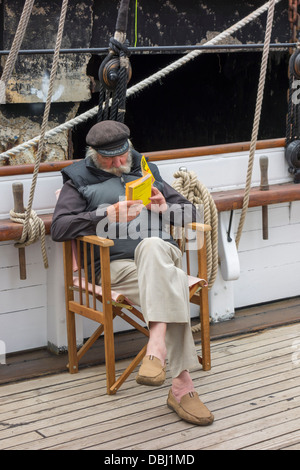 An old man sitting on a deck chair reading a book on board a ship - Stock Image