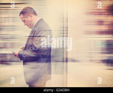 A business man in a suit is texting on his cell phone in the city outside with a wall for a communication or message - Stock Image