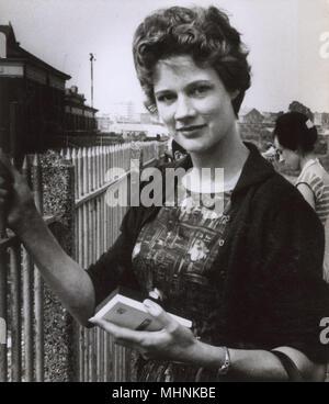 Pretty 1960s girl holding a Philips portable transistor radio.     Date: circa 1963 - Stock Image
