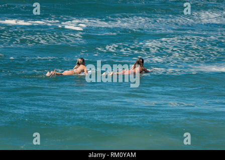 Two girls surfing in the shallows. - Stock Image