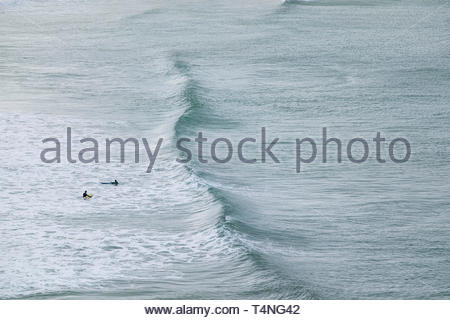 Surfers waiting for an incoming wave at Crantock Beach in Newquay in Cornwall. - Stock Image