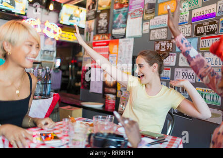 Enthusiastic young women friends cheering in bar - Stock Image