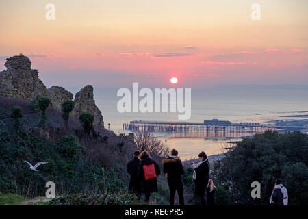 Hastings, East Sussex, UK. 20th January 2019. Walkers well wrapped up to watch the sunset from Hastings Castle at the end of a cold sunny day. - Stock Image