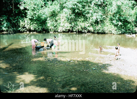 Dayak people washing and bathing in the river near their longhouses; Kuching area, Sarawak, Malaysia.  People seemed - Stock Image