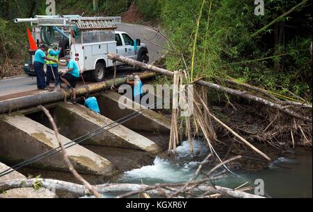 Puerto Rican Aqueduct and Sewer Authority workers fix a damaged pipeline at the Mayaguecilla River during relief - Stock Image