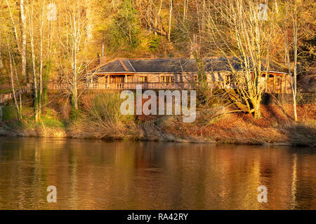 A riverside bungalow partially reflected in the River Eden, Corby Woods, Cumbria, UK - Stock Image