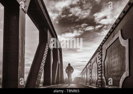 Rear view of man running over bridge at sunrise. UK - Stock Image