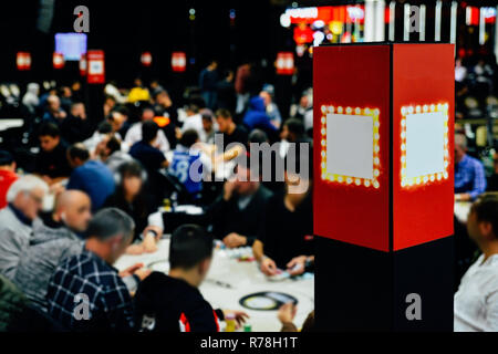 Defocused view of large multi table poker tournament. Players sitting at table and dealers dealing cards. - Stock Image