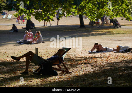 People relaxing in the sun, St James's Park, London, England, Great Britain - Stock Image
