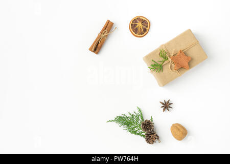 Gift box wrapped in craft paper tied with twine pine cones juniper nuts cinnamon on solid white background. New Year presents holiday preparations DIY - Stock Image