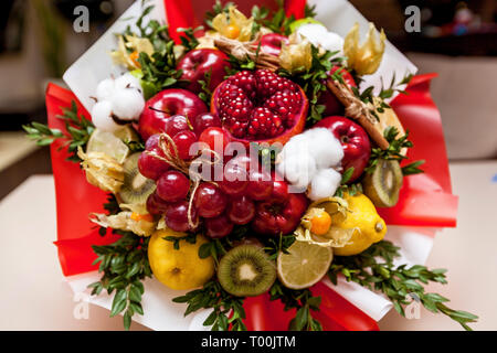 Composition of fresh bright fruits. Fruit bouquet from pomegranate, grapes, apples, kiwi, orange, lemon, brown and cotton - Stock Image