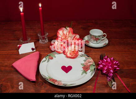 Floral pattern fine china dinnerware with matching plate, cup and saucer. bouquet of orange and white roses, pink napkin, silverware, red candles and  - Stock Image